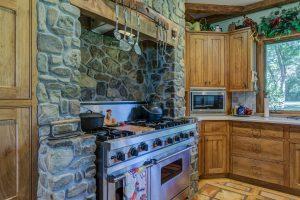 Vieille cuisine avec meubles en bois et murs en pierre