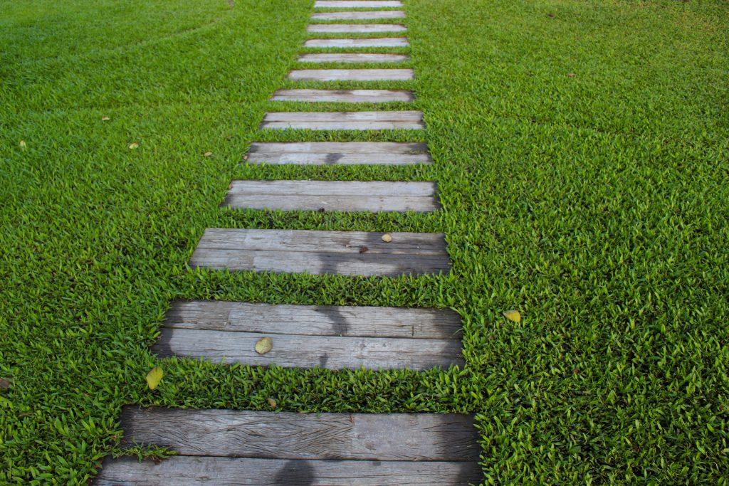 Dalles en bois formant un chemin au milieu d'une pelouse
