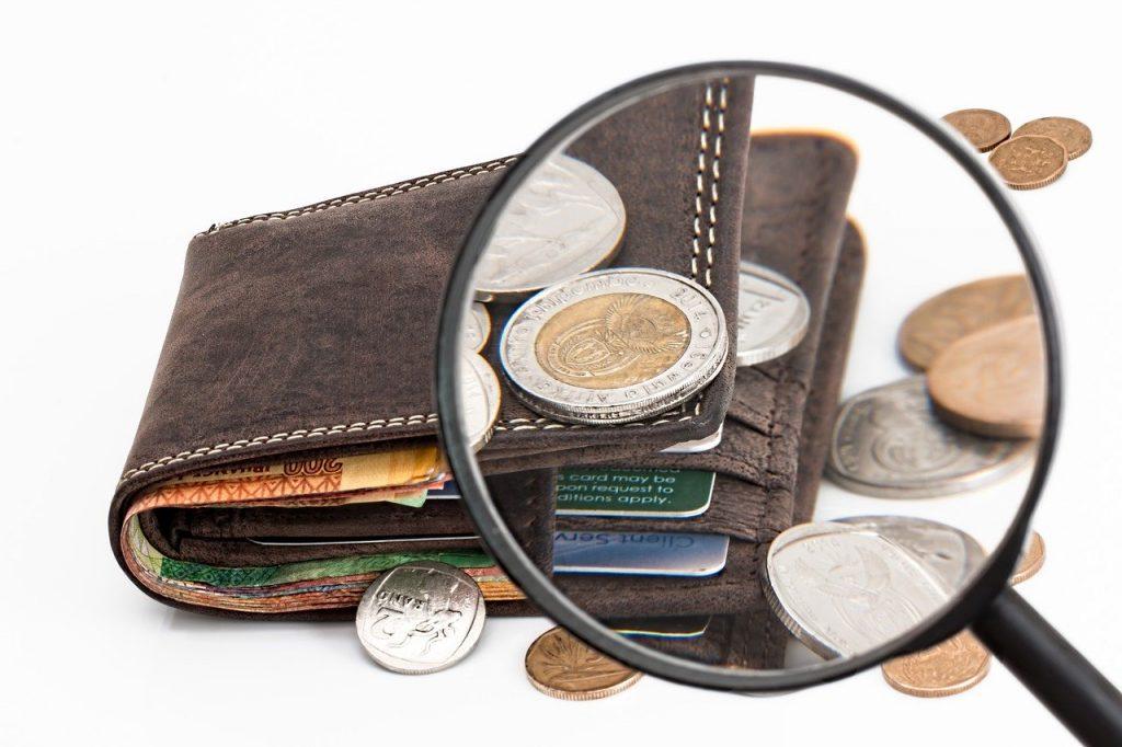 loupe sur un portefeuille rempli d'argent liquide