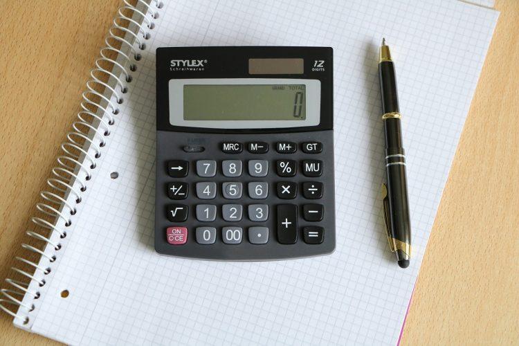 calculatrice et stylo posés sur un cahier
